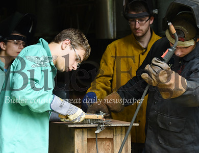Harold Aughton/Butler Eagle: Edward Ditch, 14, of New Castle brushes the wing of his Eagle prior to welding it together at Campu Bucoco.