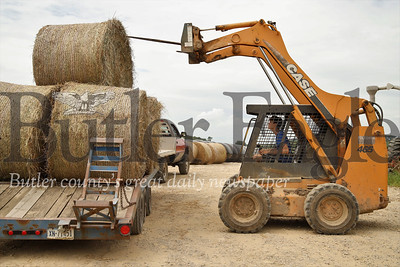 Austin Miller lines up to grab a hay bale to be wrapped in plastic. Seb Foltz/Butler Eagle