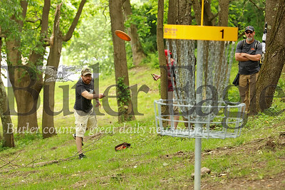 Jeff McCullough Jr. tosses a disc towards the basket on hole one at the North Boundary Park disc golf course. McCullough, his dad and friends were the first group to play through the course following Saturday's official grand opening ribbon cutting ceremony. Seb Foltz/ Butler Eagle