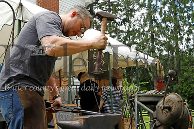 Slippery Rock blacksmithing artist Kyle Gercken of Forged in Kol hammers out what will become a decorative hook while manning his booth at Whispering Pines. Seb Foltz/ Butler Eagle