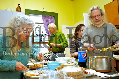 Lois Ament (left),  Hugh Barnes(right) and  members of the Ginger Hill Unitarian Universalist Congregation prepare plates at their bimonthly potluck. Seb Foltz/Butler Eagle