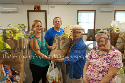 Photo by J.W. Johnson Jr.Sharon Klaiber, director of the Southwest Butler Food Cupboard, distributes food to residents William Hildenbrand, Norma Wright and Cathy Ohler.
