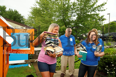 Krista Novak (left) and Amy Rubinosky load books into the new book boxes in Evan City by the EDCO Park Pool. Seb Foltz/Butler Eagle