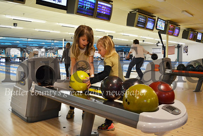 Mckenna Scott, 6, left, and Madisyn Lawniczak, 3, pick up a bowling ball during the Strike Out Child Abuse Bowling Event Sunday at Family Bowlaway. Photo by Joe Genco.