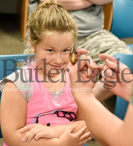 Harold Aughton/Butler Eagle: Bria Gerber, 6, of Butler reacts to Bob, a Madagascar Hissing Cockroach at the Butler Library, Wednesday, June 26.  Erie Zoo volunteer Peggy Seib and education coordinator Grace Lewis brought the children's books to life with animal ambassadors Bob, a Madagascar Hissing Cockroach;  DeWight, a prehensile-tailed Skink;  Suzy, the Ferret; and Fern, a Collared Dove