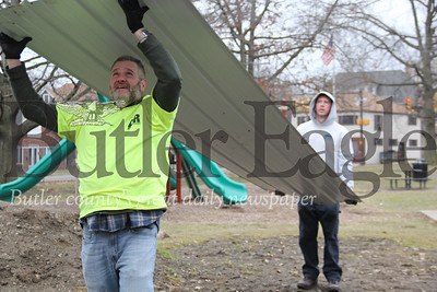 Glenn Cummings in front and Zack Birckbichler both of Butler and both members of Action in Recovery work together to lift up roofing to the men working on securing the panels to the roof of the pavilion being built in Island Park early in the morning on March 2, 2019.Photos by Lauryn Halahurich/Butler Eagle
