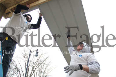 Zack Birckbichler of Butler, right, and Alexander Robertson of Butler, both members of Action in Recovery, lift and guide a roof panel up onto the top of pavilion being built in Island Park early in the morning on March 2, 2019. Photos by Lauryn Halahurich/Butler Eagle