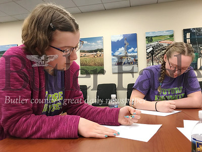 Butler Intermediate High School seventh-graders Katie White, 13, and Maddy Harbison, 13, draw a design and write down supplies for the launcher their team would have to create.