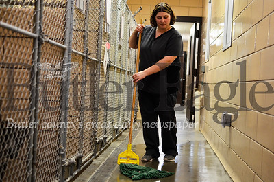 Shanna Best, kennel director for the Butler County Humane Society, mops the organization's in-take area. Best and fellow staff members spent much of Wednesday repeatedly sanitizing the facility as a batch of abused dogs were brought in. Tanner Cole/Butler Eagle