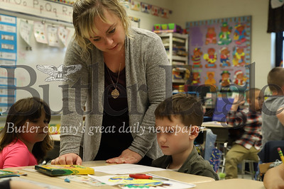 First grade teacher Rene Ruffner helps Arian Herp with his Mother's Day letter.  Kaylea Parker also pictured. Seb Foltz/Butler Eagle