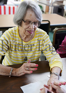 Harold Aughton/Butler Eagle: Trista Fischer, 25, a student at the Butler Beauty School, paints the finger nails of Maxine Craig, 87, of Chicora, Thursday, May 10, at the Chicora Senior Center.