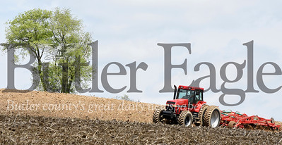 Harold Aughton/Butler Eagle: Roudy Roudebush, a labor for Steve Geibel Farm near Chicora, plows under last year's corn field in preparation for spring planting...