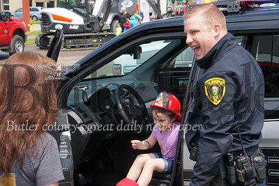Photo by J.W. Johnson Jr. Dakota Delduca of Economy sits in a Zelienople police vehicle while Patrolman Bret Myers assists her Saturday at the annual Big Truck Day in Zelienople Community Park.