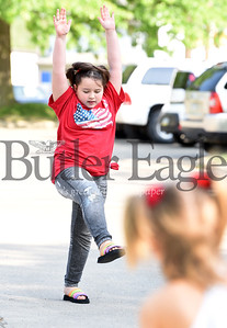 Harold Aughton/Butler Eagle: Dahlia Carson,5, watches as her sister Vyolet, 8, prepares to do a cartwheel in the parking lot of the City of Butler Farmers' Market, Saturday, May 25, 2019. The market will be open at 8:00 a.m. - 1:00 p.m. every Saturday through the end of October.