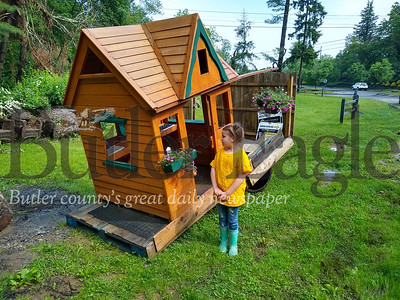 Lilly Elliott, 8, stands next to her play house which was washed around the family's residence at 300 Denny Road, Middlesex Township, during the storm last night. Lilly, her two siblings and her aunt were rescued by kayak Wednesday night from the home of her grandmother, Karla Horanic.Donna Sybert/ Butler Eagle