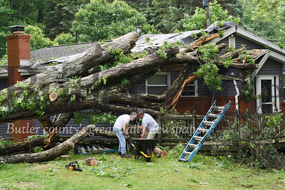 Harold Aughton/Butler Eagle: Joel Sarson, 80, (on left) and Dave Matko work together to remove remanants of anearly 60 ft. oak tree that landed on the house of Larry and Jill Matko of 153 Cashdollar Road Wednesday morning.