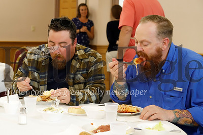Matthew Reisinger(left) and Josh Meeder of Harmony enjoy a free dinner put on by volunteers at Grace Church of Harmony Wednesday evening, following Tuesday night's flooding.