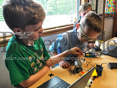 Joel Shaffer, 9, and Bryan Kenyon, 7, work to make their bees waddle using coding at the Kid's Innovation Playground in Slippery Rock. Photo by Gabriella Canales