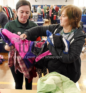 Harold Aughton/Butler Eagle: Service coordinators Tori Hesidence, left, and Barb Sarvey, for the Community Resource Center, inspect and sort coats prior to giving them away during the Bundle up Butler Event, Tues., Oct. 30.
