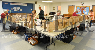 Harold Aughton/Butler Eagle: Volunteers  (left - right) Ruth Stiltz,Carol Bahorich, Fred Berns, Norah Collins and Karen Shultz at  St. Peter's Anglican Church prepares bags for delivery, Thurs., Oct. 31.