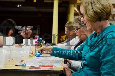 Paula Thomas marks numbers off a bingo card at the fourth annual Paw Print Basket Bingo at Highfield Hall. The event benefits Operation Spay Neuter. Tanner Cole/Butler Eagle