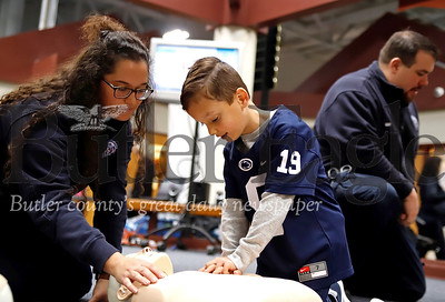 Vincent Mimran, 6, lerns the basics of hands-only CPR from a Cranberry EMS member  at the Cranberry Township Municipal Center Saturday. Cranberry EMS hosted their annual Save-A-Life Saturday giving anyone in attendence a free basic CPR lesson and celebrating the lives of a few area residents who were saved by good samaritans that started CPR before EMS arrived.  Mimran's grandfather Gary Lucente was among those in attendance who had been revived  by CPR after going into cardiac arrest. Lucente was in a Cranberry area shopping center when he suffered heart failure and Cranberry EMS responded. Seb Foltz/Butler Eagle