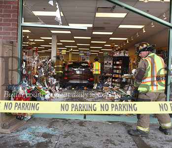 Harold Aughton/Butler Eagle: A Butler Twp. fireman cleans up the broken glass from the Hallmark store front after a woman drove her Honda CR-V through it.