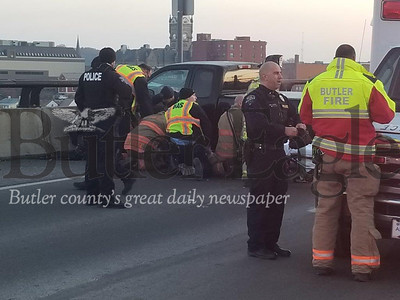 Jim Smith photo Emergency crews rescue a woman injured about 7 a.m. Friday when the pickup truck she was driving struck the side of the Route 8 bridge in Butler. The woman suffered an apparent dislocated knee, authorities said. 3 col. pic