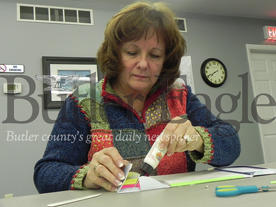 Nancy Rodgers, of Butler, glues together a handmade pocket book for the Happy Stampers craft of the month. Photo by Gabriella Canales.