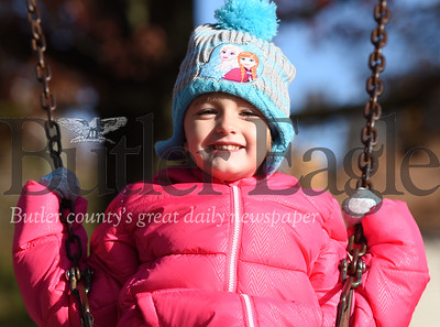 Harold Aughton/Butler Eagle: Grace Scott, 4, of Butler rides the swings in Rotary Park Sunday afternoon as members of the Victory Church served hot meals and handed out frozen turkeys.