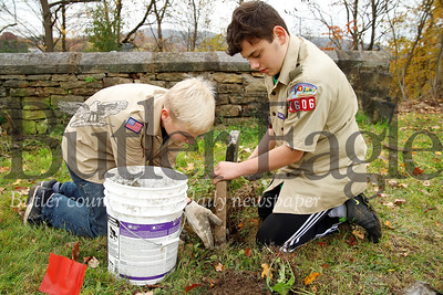 Jessie James Martineau, 14, helps Tyler Rasmussen, 13, fix a grave stone in the Harmony Mennonite Meetinghouse  Cemetery in Harmony. Martineau and Rasmussen and two other scouts from Boy Scout Troup 1606 worked on fixing up the cemetary for their Eagle Scout projects. Seb Foltz/Butler Eagle