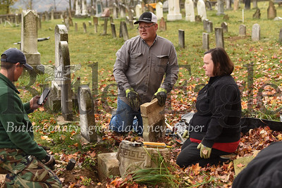 Jason Martineau (center) and other parents prepare to remount a fallen tombstone  in the Harmony Mennonite Meetinghouse  Cemetery. Martineau and other parents helped their sons' Boy Scout Troup 1606 fixing up the cemetary for their Eagle Scout projects. Seb Foltz/Butler Eagle