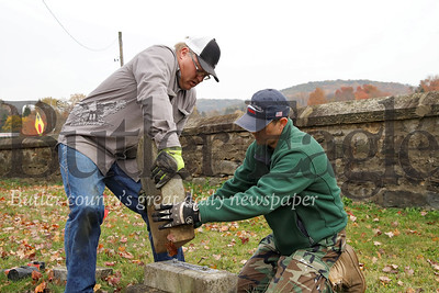 Jason Martineau (left) and Sam Jones remount a fallen tombstone  in the Harmony Mennonite Meetinghouse  Cemetery. Martineau and Jones were helping their sons' Boy Scout Troup 1606 fixing up the cemetary for their Eagle Scout projects. Seb Foltz/Butler Eagle