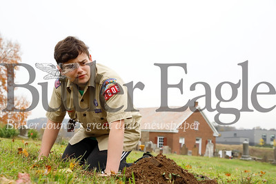 Tyler Rasmussen, 13, judges the size of a hole to decide if it is large enough to remount a fallen tombstone in the Harmony Mennonite Meetinghouse  Cemetery. Rasmussen and three other scouts from Boy Scout Troup 1606 worked on fixing up the cemetary for their Eagle Scout projects. Seb Foltz/Butler Eagle