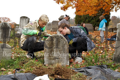 Gator Martineau (left) and Sadie Jones pour mortar to fix a grave stone in the Harmony Mennonite Meetinghouse  Cemetery in Harmony. Martineau and three other scouts from Boy Scout Troup 1606 worked on fixing up the cemetary for their Eagle Scout projects. Seb Foltz/Butler Eagle