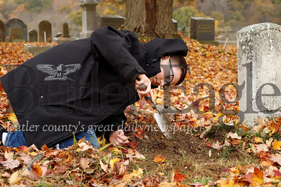 Greyson Jones, 14, clears dirt around the base of a fallen tombstone in the Harmony Mennonite Meetinghouse  Cemetery. Martineau and Rasmussen and two other scouts from Boy Scout Troup 1606 worked on fixing up the cemetary for their Eagle Scout projects. Seb Foltz/Butler Eagle