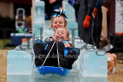 Jadelynn Broerman, 7, and Malayna Smith, 9, test ride the ice slide at Cranberry Cranberry Township Municipal Building Wednesday. A crew from DiMartino Ice Company built the slide in preparation for for Cranberry Township's Santa's First Stop Eagle North Pole Ice Festival Friday. Seb Foltz/Butler Eagle