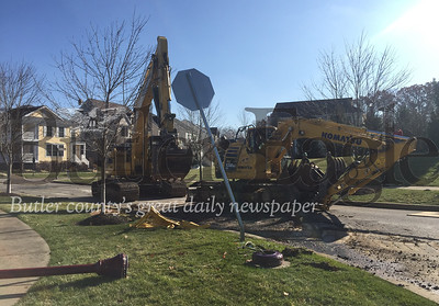 An overturned mid-sized excavator blocked the entry to Park Place on Powell Road Monday. Alex Weidenhof/Butler Eagle
