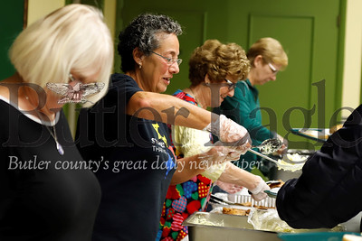 Cindy Schmidt serves up a scoop of mashed potatoes  at St. Paul Roman Catholic Church community dinner Tuesday night in Butler. Seb Foltz/Butler Eagle