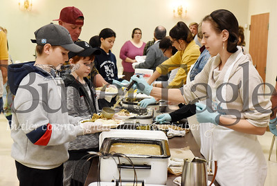 Harold Aughton/Butler Eagle: Jacob Oplinger, 13, of Butler (left) and Abbey Klingler, a junior at Point Park University, volunteered to serve members of the community at St. Peter Catholic Parish Hall, Thurs., Nov. 28, 2019.