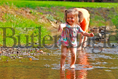 Jeslynn Shoaf, 2, and her brother Blaise Odom, 10, beat the heat Tuesday afternoon playing in the creek at Butler's Memorial Park. Temperatures kissed highs in the low 90s in the region, matching a high temperature record dating back to the 1880s. Seb Foltz/Butler Eagle