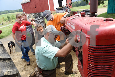 Harold Aughton/Butler Eagle: Guy Daubenspeck starts a lesson on how to change spark plugs in a 1950 Farmall C as students, Brady Stewart, 14, Lily Zang, 6, Robyn Freund, 17, and Emily Zang look on..
