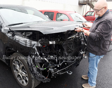 Harold Aughton/Butler Eagle: Paul McCall of Joe Pierrel Auto, examines the damage on a Jeep Cherokee caused by a deer Mon. Oct 7.