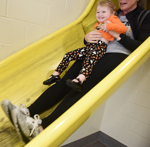 Harold Aughton/Butler Eagle: Iris Edwards, 2, of Mars slides down the Adams Firefighters slide with her mother Bethany, following the Mars Library's story time held at the Adams Fire Station, Tues. Oct. 8.
