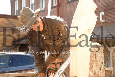 Steve Nelson works on a chainsaw wood carving sculpture at Zelienople Fall Festival Saturday. Seb Foltz/Butler Eagle 2019