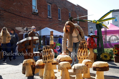 Zelienople Fall Festival attendees peruse chainsaw carving sculptures from The Cutt'N Hut chainsaw carvings by Steve Nelson. Seb Foltz/Butler Eagle 2019