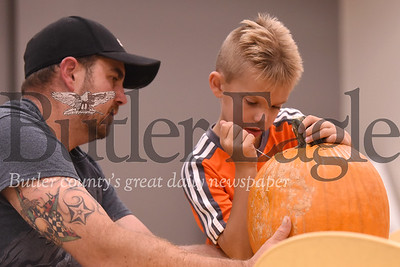 Parker Knobeloch, 7,  of Butler carves his pumpkin with his dad Bob Knobeloch. Seb Foltz/Butler Eagle