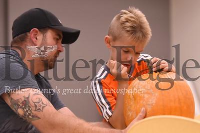 Parker Knobeloch, 7,  of Butler carves his pumpkin with his dad Bob Knobeloch. Seb Foltz/Butler Eagle
