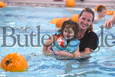 Alexis Smith, 5, swims toward her pumpkin with the help of her mom Apri at the Butler YMCA Floating Pumpkin Patch event Saturday. Seb Foltz/Butler Eagle