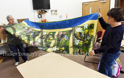 Harold Aughton/Butler Eagle: Volunteers Robin Brown of Connoquennessing Twp. and Judy Fedosick of Bulter, work together in storing a quilt for the upcoming quilt show at Lutherlyn Sat. Oct. 19 and Sun., Oct. 20.